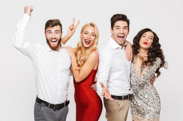Image d'un jeune groupe d'amis excité debout isolé sur blanc faire un geste drôle de paix.