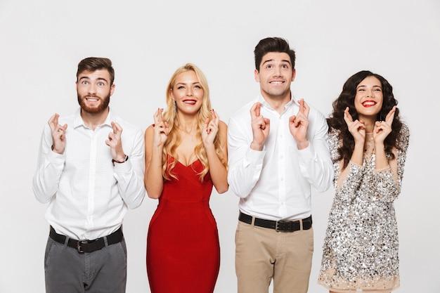 Image d'un jeune groupe d'amis excité debout isolé sur blanc faire un geste d'espoir.