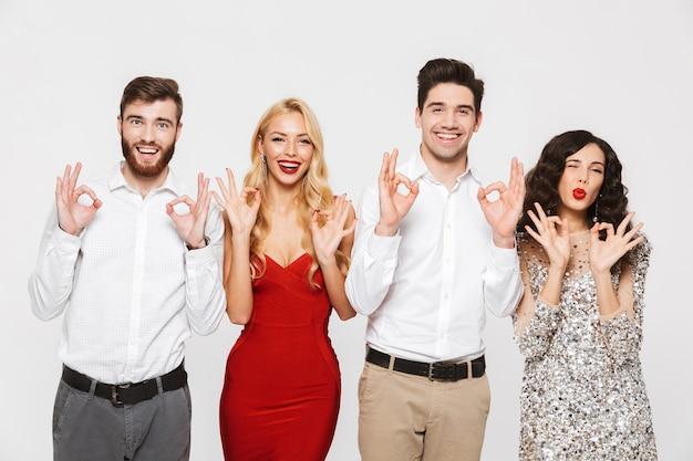 Image d'un jeune groupe d'amis heureux debout isolé sur blanc montrant un geste correct.
