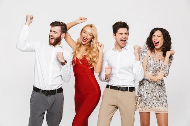 Image d'un jeune groupe d'amis heureux debout isolé sur blanc montrant le geste du gagnant.