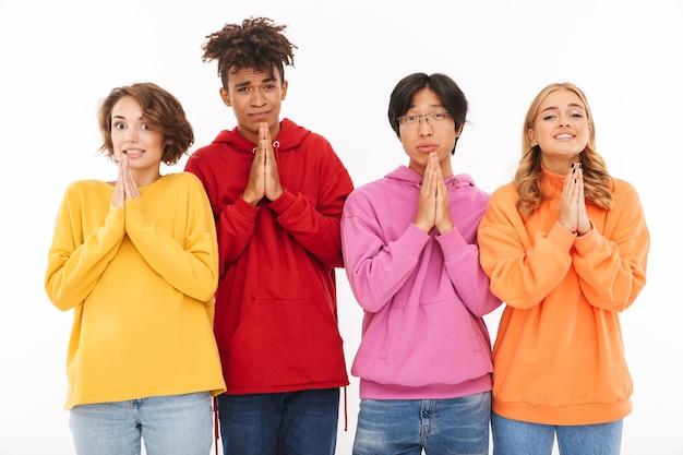 Image d'un jeune groupe d'étudiants amis debout isolé, montrant le geste de prier.