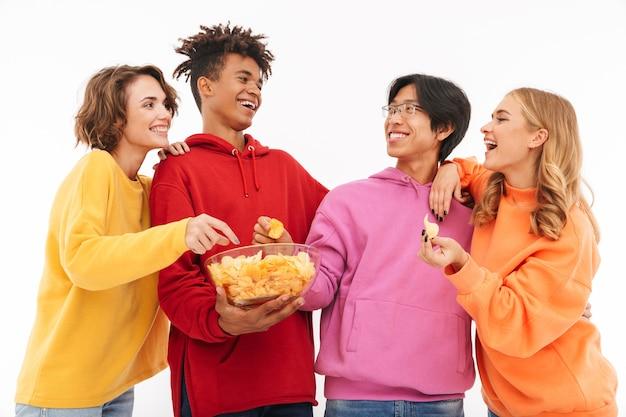 Image d'un jeune groupe d'étudiants amis debout isolés, parlant les uns avec les autres, mangent des chips.