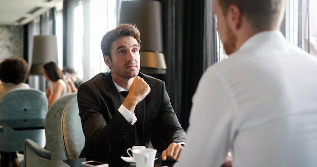 Image d'un jeune homme d'affaires avec une tasse de café communiquant avec son collègue