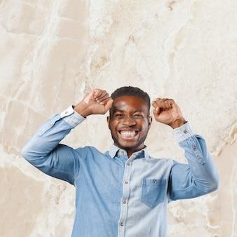 L'image d'un jeune homme africain heureux debout fait un geste gagnant.