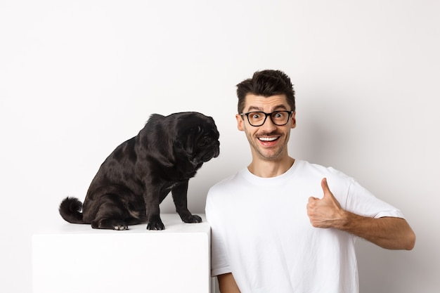 Image d'un jeune homme heureux et satisfait assis près d'un chien carlin et montrant le pouce levé, souriant et louant un bon produit, fond blanc