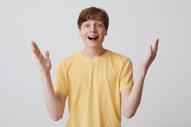 L'image d'un jeune homme heureux se sent heureux et des kilomètres à la ronde. il garde les mains levées et attend de bonnes nouvelles concernant ses examens. isolé sur mur blanc