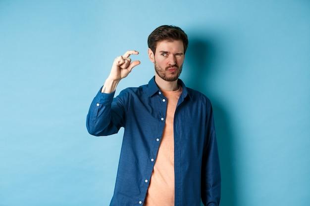 Image d'un jeune homme de race blanche montrant une petite taille et plissant les yeux pour voir quelque chose de minuscule, debout sur fond bleu.
