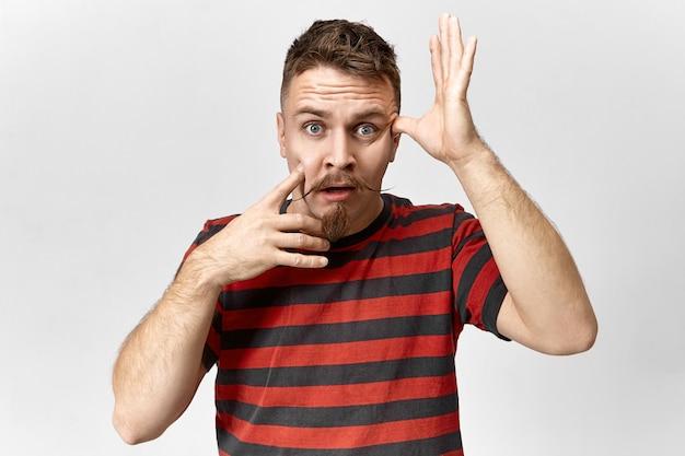 Image d'un jeune homme séduisant avec une moustache de guidon et une barbe de barbiche ayant un regard panique oublié, regardant la caméra avec la bouche ouverte, oublié de faire quelque chose de très important. sentiments humains