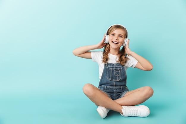 Image d'une jeune petite fille assez heureuse posant isolée sur une musique d'écoute bleue avec des écouteurs.