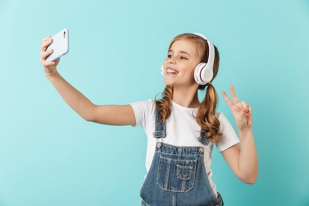 Image d'une jeune petite fille assez heureuse posant isolée sur un selfie de walltake bleu par téléphone en écoutant de la musique avec des écouteurs.