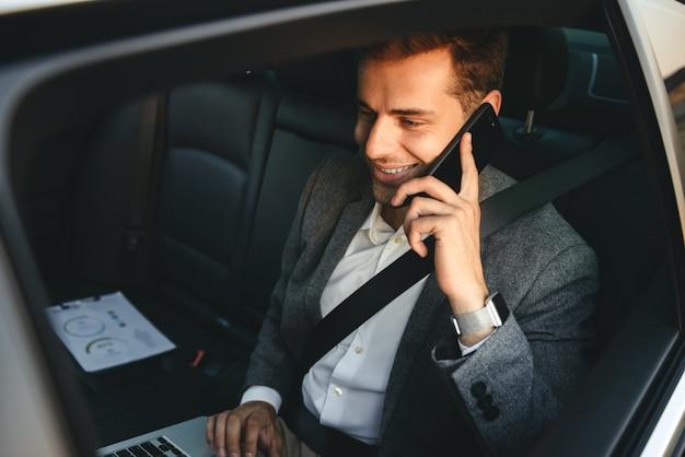 Image d'un jeune réalisateur en costume parlant sur smartphone et travaillant sur ordinateur portable, assis à l'arrière dans une voiture de classe affaires avec ceinture de sécurité