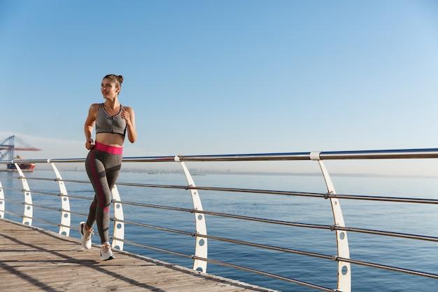 Image de jeune sportive en bonne santé jogging près du bord de mer.