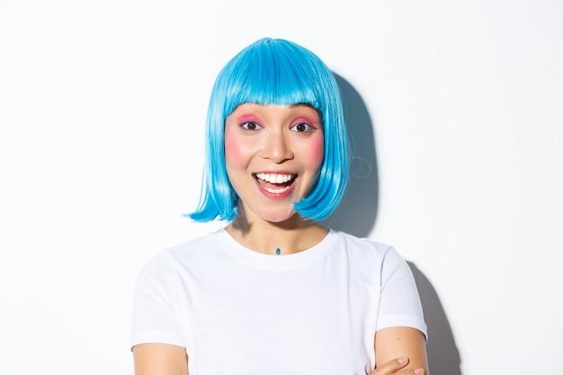 Image de jolie fille asiatique excitée en costume d'halloween et perruque bleue, souriant amusé, debout.