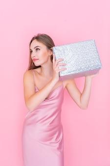 Image d'une jolie fille secouant une boîte avec un cadeau qui se demande ce qui se trouve à l'intérieur de la boîte emballée sur fond rose