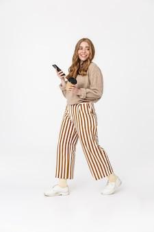 Image d'une jolie jeune adolescente souriante et souriante marchant isolée sur un mur blanc à l'aide d'un téléphone portable buvant du café.