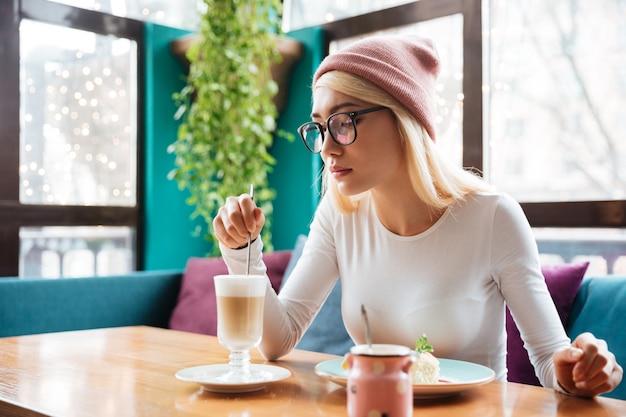 Image de jolie jeune femme portant un chapeau et des lunettes, manger un gâteau et boire du café tout en étant assis dans un café.