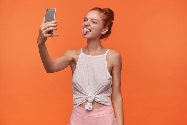 Image de jolie jeune femme portant ses cheveux foxy en noeud, gardant le smartphone en main et regardant la caméra avec une grimace, duper à la caméra et montrant la langue, isolée sur fond orange