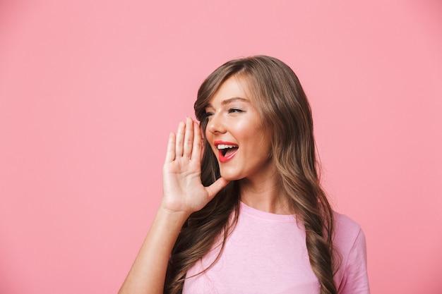 Image de joyeuse femme européenne avec de longs cheveux bruns bouclés regardant de côté à copyspace et en criant ou en appelant quelqu'un, isolé sur fond rose