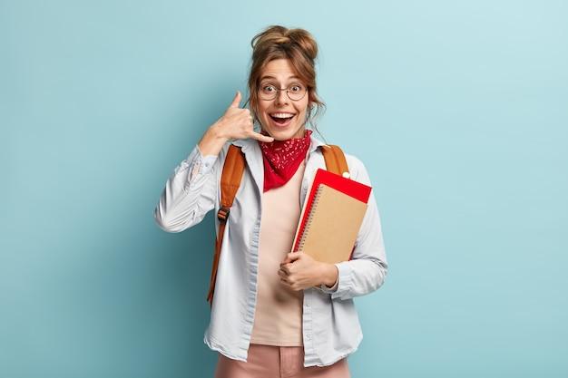 Image de joyeuse jeune femme fait un geste de téléphone, porte une chemise et un bandana rouge