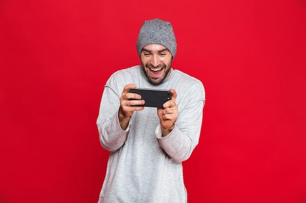 Image de joyeux homme 30 s tenant un smartphone et jouer à des jeux vidéo, isolé