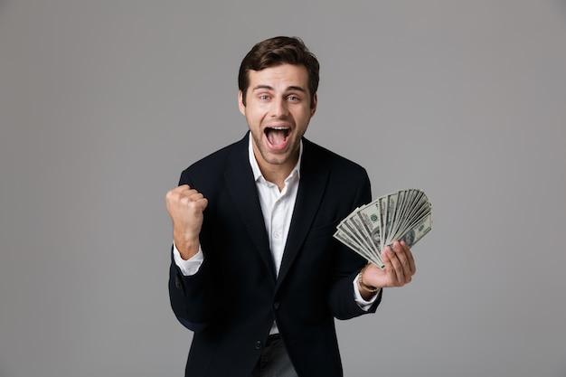 Image de joyeux homme d'affaires des années 30 en costume souriant et tenant un ventilateur d'argent comptant, isolé sur mur gris