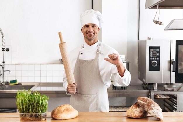 Image de joyeux homme boulanger en uniforme blanc souriant, debout à la boulangerie avec du pain sur la table