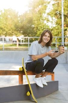 Image de joyeux jeune patineur assis dans le parc avec planche à roulettes à l'aide de téléphone portable, boire du café.