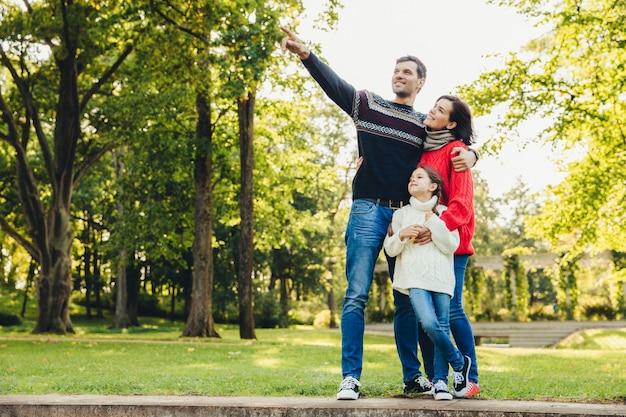 Image de joyeux joyeux jeune père de famille, mère et petite fille jouent ensemble dans un parc en automne