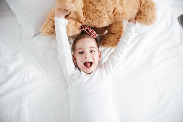 Image de joyeux petit garçon se trouve sur le lit à la maison tenant un ours en peluche. regardez devant.