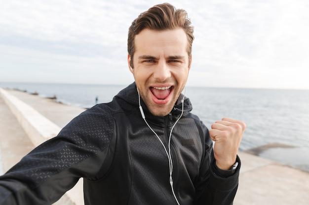 Image de joyeux sportif des années 30 en vêtements de sport noirs et écouteurs, prenant une photo de selfie sur un téléphone mobile tout en marchant au bord de la mer