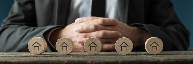 Image large d'un homme d'affaires ou d'un agent immobilier assis à un bureau avec cinq cercles en bois coupés avec des icônes de maison placées dans une rangée devant lui.