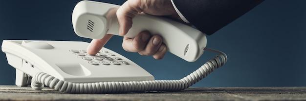 Image large vue d'homme d'affaires composant le numéro de téléphone sur le téléphone fixe blanc tout en tenant un combiné. sur fond bleu marine.