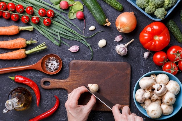 Image sur des légumes frais, des champignons, une planche à découper, de l'huile, un couteau, des mains de cuisinier