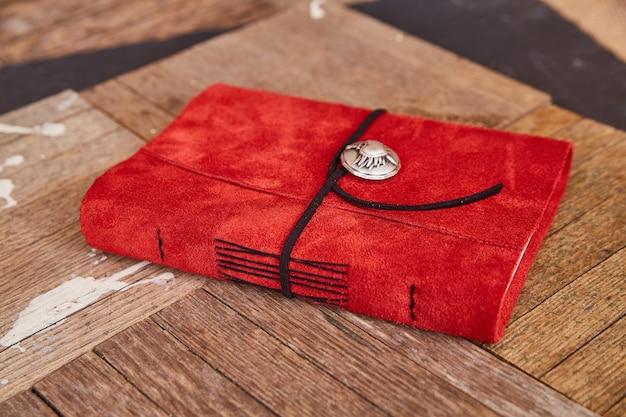 Image d'un livre en cuir rouge artisanal avec du fil noir sur des planches de bois