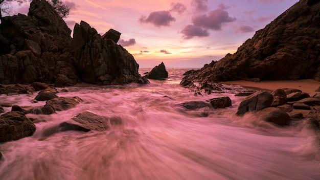 Image de longue exposition de paysage marin ciel dramatique avec rocher en arrière-plan de paysage coucher de soleil
