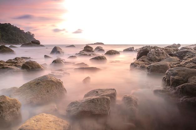 Image de longue exposition sur paysage de pierre et de coucher de soleil sur la mer d'andaman