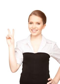 Image lumineuse d'une belle blonde montrant le signe de la victoire