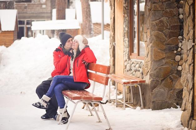 Image lumineuse du couple de famille dans un vêtement d'hiver assis sur un banc en bois