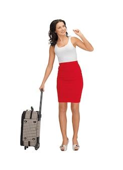 Image lumineuse d'une femme faisant de l'auto-stop avec une valise