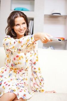 Image lumineuse d'une femme heureuse avec une télécommande de télévision
