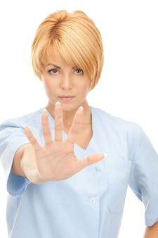 Image lumineuse d'une femme médecin séduisante montrant un geste d'arrêt