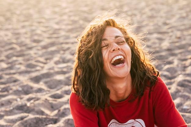 Image lumineuse d'une femme qui rit sur la plage