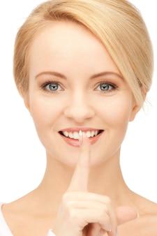 Image lumineuse de jeune femme avec le doigt sur les lèvres