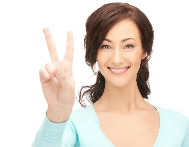 Image lumineuse de la jeune femme montrant le signe de la victoire