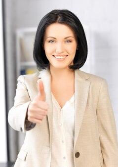 Image lumineuse de jeune femme avec les pouces vers le haut