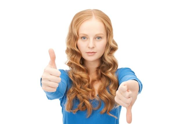 Image lumineuse d'une jolie adolescente avec les pouces vers le haut et vers le bas