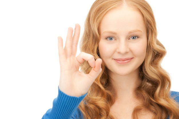 Image lumineuse d'une jolie femme montrant un signe ok