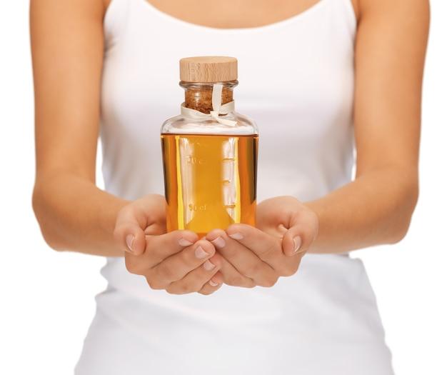 Image lumineuse de mains féminines avec une bouteille d'huile