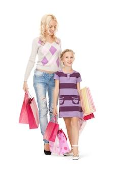 Image lumineuse d'une mère heureuse et d'une petite fille avec des sacs à provisions