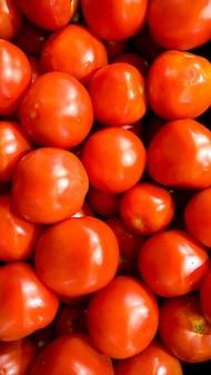 Image macro de beaucoup de petites tomates cerises rouges sur le comptoir au magasin de légumes. texture ou motif de légumes mûrs frais